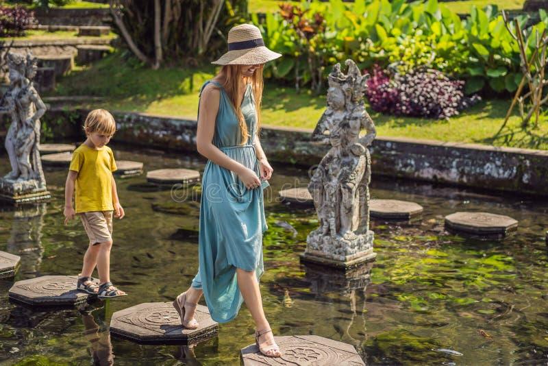 Turisti del figlio e della mamma in Taman Tirtagangga, palazzo dell'acqua, parco dell'acqua, Bali Indonesia Viaggiando con il con immagine stock libera da diritti