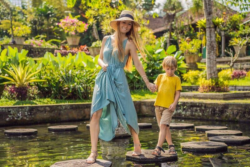 Turisti del figlio e della mamma in Taman Tirtagangga, palazzo dell'acqua, parco dell'acqua, Bali Indonesia Viaggiando con il con fotografia stock