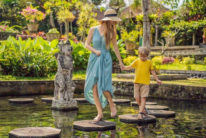 Turisti del figlio e della mamma in Taman Tirtagangga, palazzo dell'acqua, parco dell'acqua, Bali Indonesia Viaggiando con il con fotografia stock libera da diritti