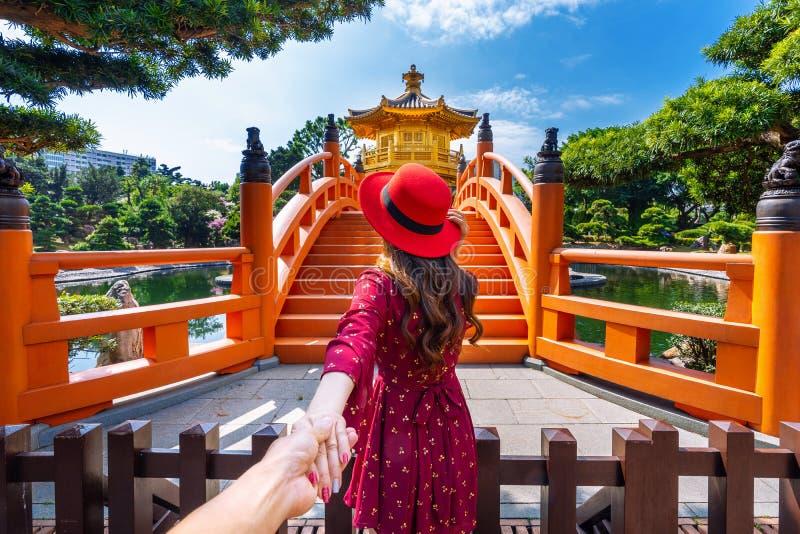 Turisti delle donne che tengono la mano dell'uomo e che lo conducono al padiglione dorato in Nan Lian Garden vicino al tempio di  fotografia stock