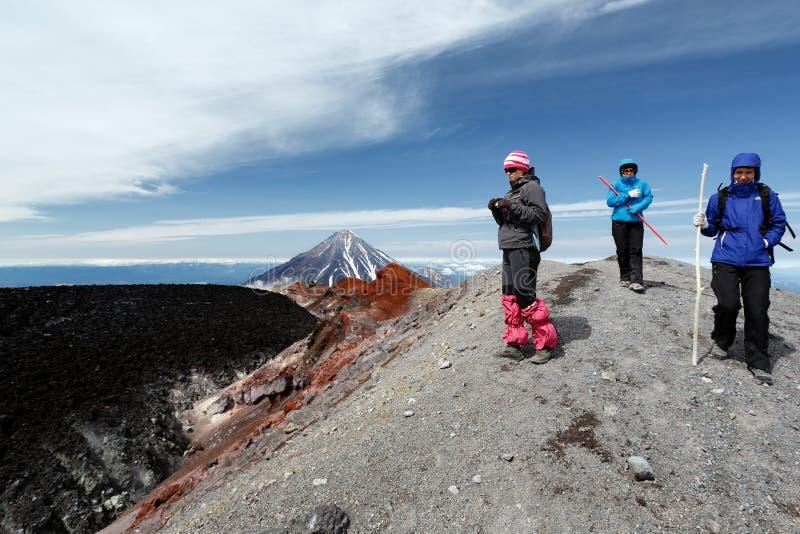 Turisti delle giovani donne che camminano sulla traccia di escursione della montagna sul cratere fotografia stock