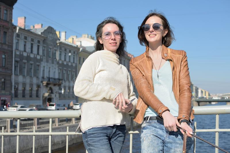 Turisti delle giovani signore nei selfies della presa di San Pietroburgo Russia su un ponte di legno nel centro urbano storico immagine stock libera da diritti
