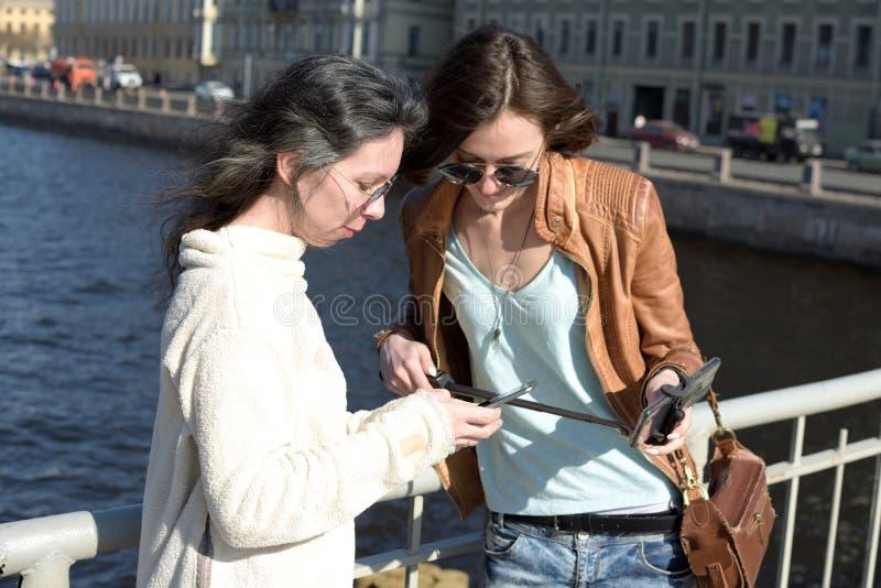 Turisti delle giovani signore nei selfies della presa di San Pietroburgo Russia su un ponte di legno nel centro urbano storico fotografie stock