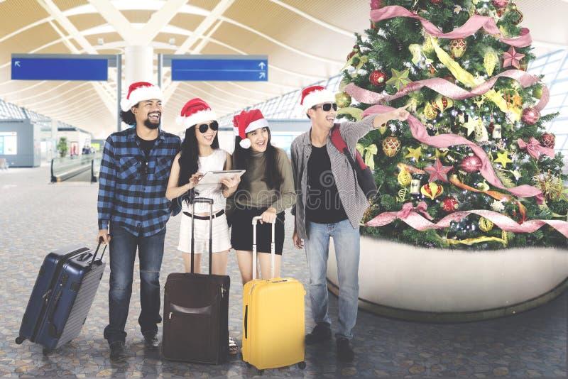 Turisti di diversità con il cappello di Santa all'aeroporto fotografia stock