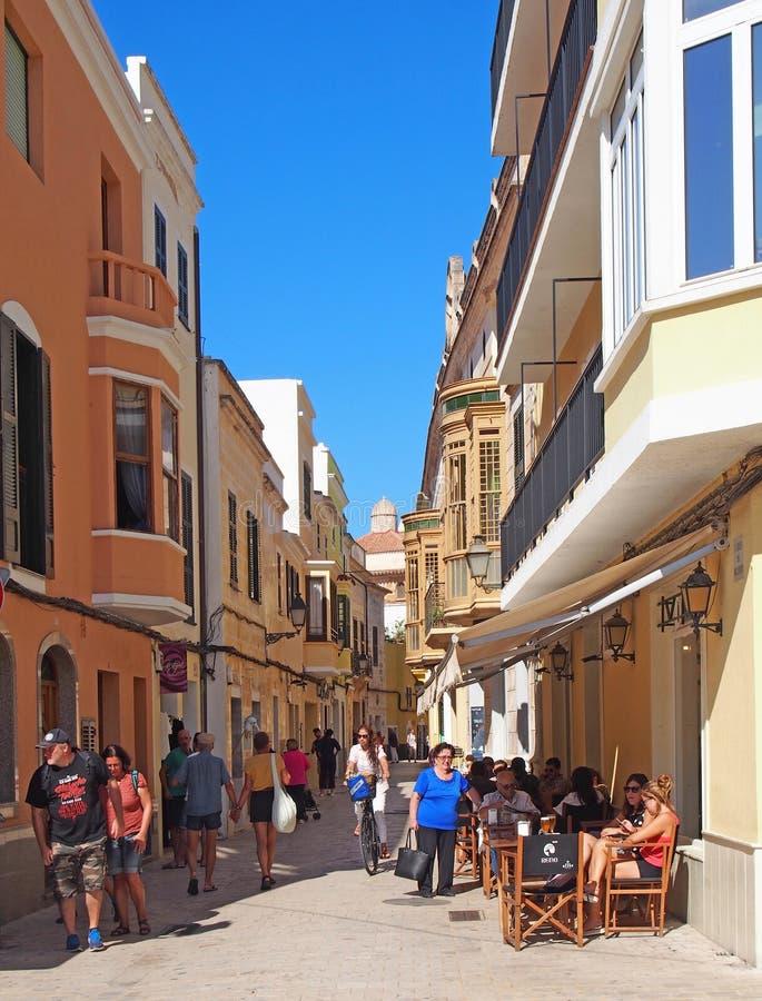 Turisti e clienti che camminano e che si siedono in un caffè all'aperto nella via nel centro città di Ciutadella Menorca fotografia stock libera da diritti