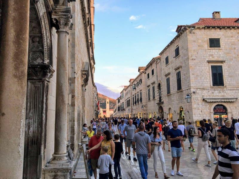 Turisti e locali che camminano giù la via principale occupata in pieno dei ristoranti e dei negozi su una sera piacevole di estat immagine stock