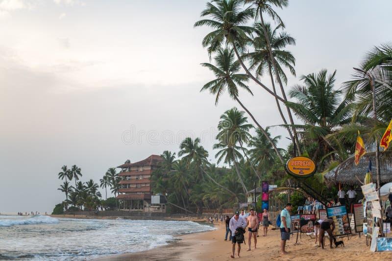 Turisti e vacanzieri sulla sabbia della spiaggia in Hikkaduwa, vicino all'Oceano Indiano fotografia stock libera da diritti