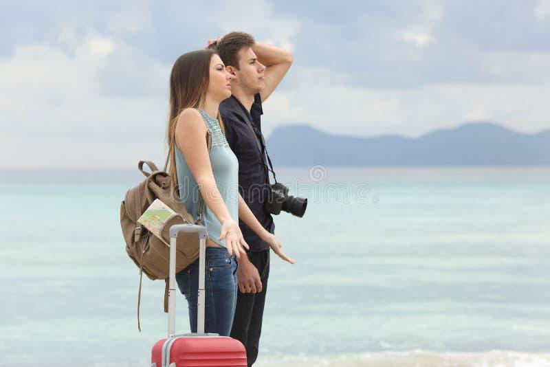 Turisti frustrati con il maltempo sulla spiaggia immagine stock