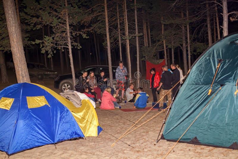 Turisti intorno al fuoco di accampamento alla notte fotografia stock