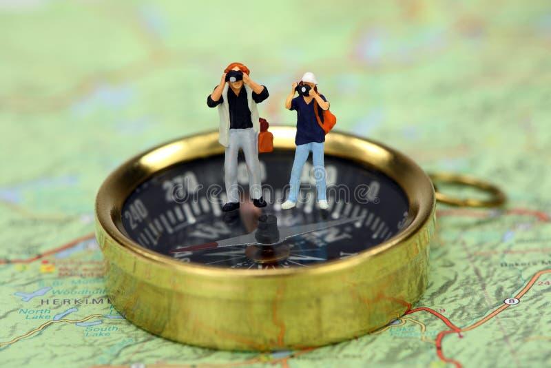 Turisti miniatura che catturano le maschere su una bussola fotografie stock