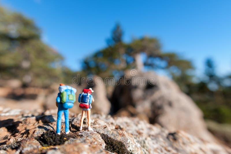 Turisti miniatura con lo zaino fotografia stock libera da diritti