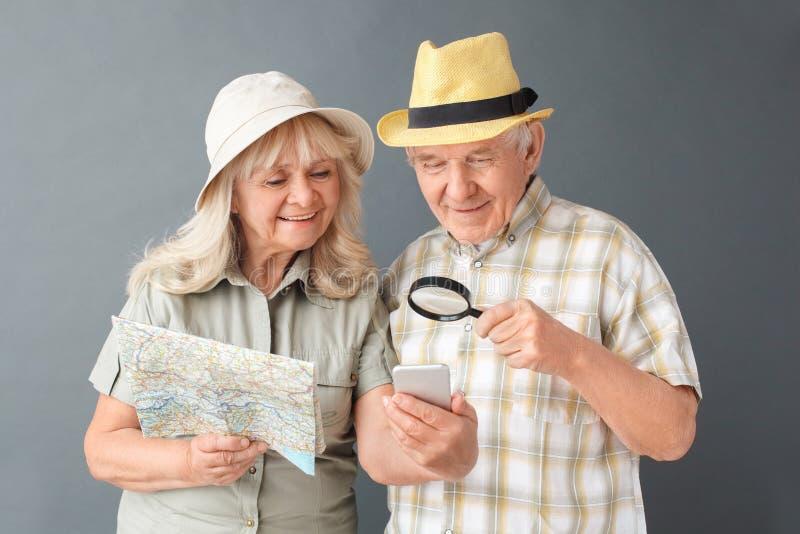 Turisti senior nella condizione dello studio dei cappelli della spiaggia isolati su grigio con la mappa che esamina smartphone tr immagine stock libera da diritti