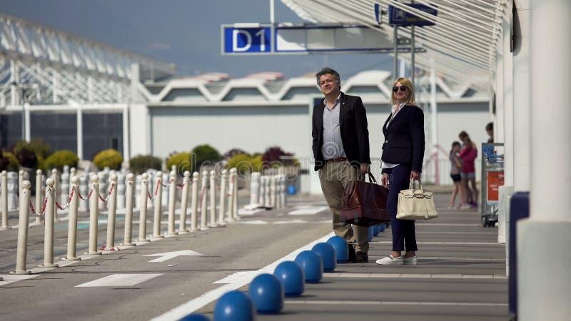Turisti stranieri con le borse che aspettano il bus di navetta vicino all'uscita del terminale di aeroporto fotografie stock