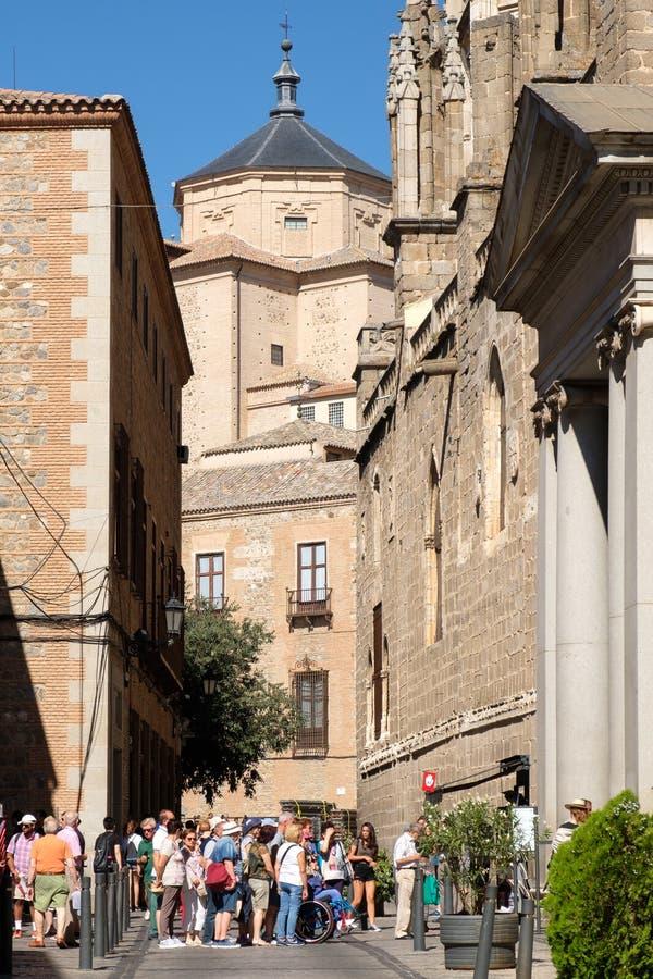 Turisti su una via stretta accanto alla cattedrale a Toledo in Spagna fotografia stock