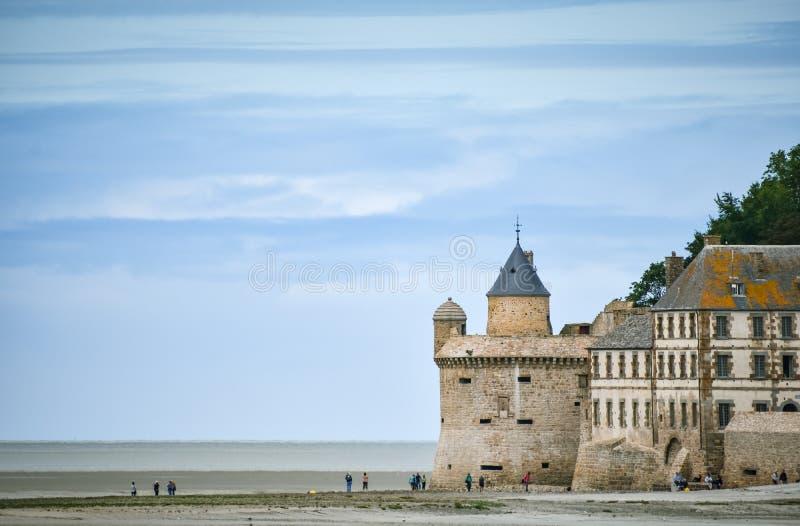 Turisti sulla spiaggia e su quella delle torri della parete di Mont Saint Michel, Francia fotografia stock libera da diritti