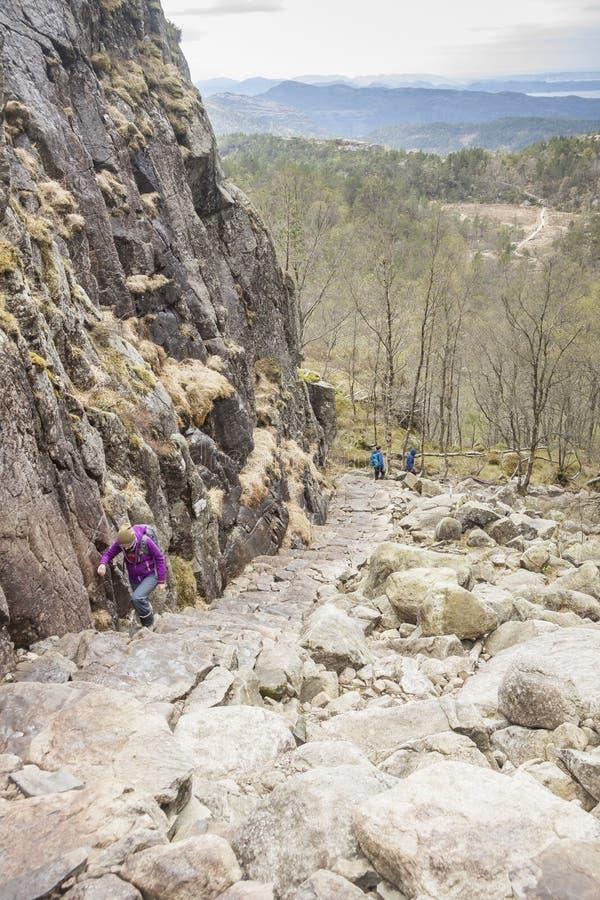 Turisti sulla traccia alla scogliera di Preikestolen - Norvegia immagini stock libere da diritti