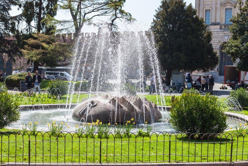 Turisti vicino alla fontana delle alpi sul reggiseno della piazza fotografia stock