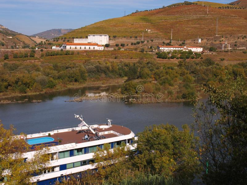 Turistic boat on Douro river Portugal. Turistic boat cross Douro river at city of Régua.View on vineyards meadows and wine caves on riverside stock image