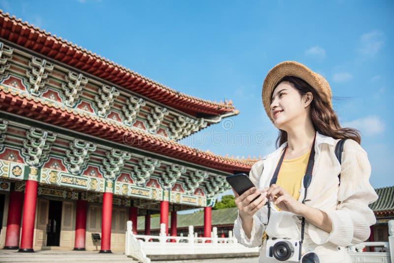 Turistkvinna med smart telefon som söker resinformation om templet royaltyfria foton