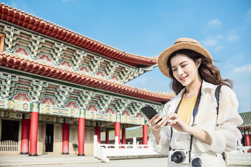 Turistkvinna med smart telefon som söker resinformation om templet royaltyfria bilder