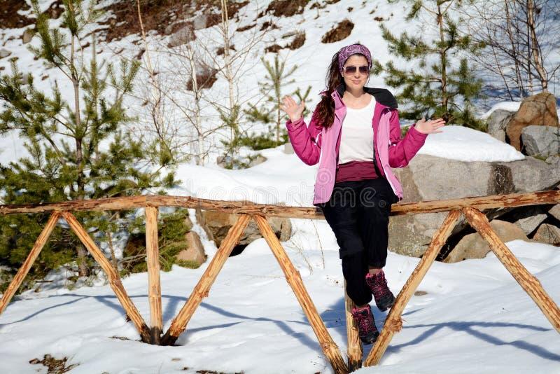 Turistkvinna som sitter och tycker om vintersolen arkivfoto