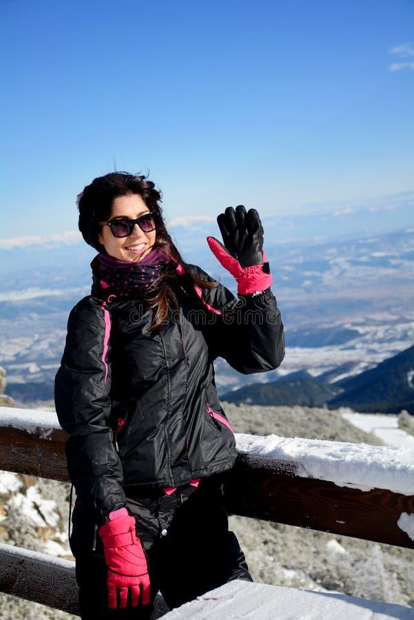 Turistkvinna som tycker om vinterbergsikten och vinkar för farväl royaltyfri foto