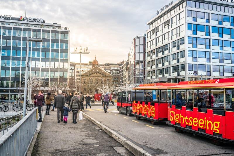Turisttåget med folk på gatan i den gamla staden med Fusterie-kyrkan i Genève Schweiz royaltyfri foto