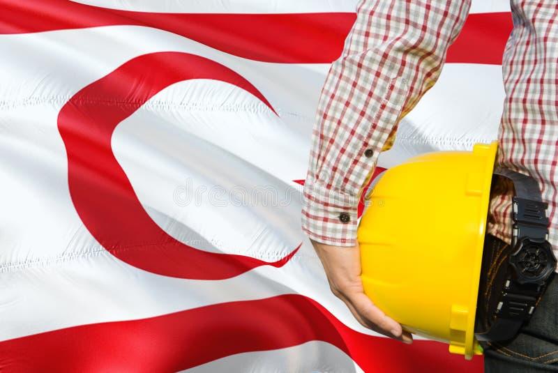 Turk Engineer está guardando o capacete de segurança amarelo com ondulação do fundo do norte da bandeira de Chipre Conceito da co foto de stock