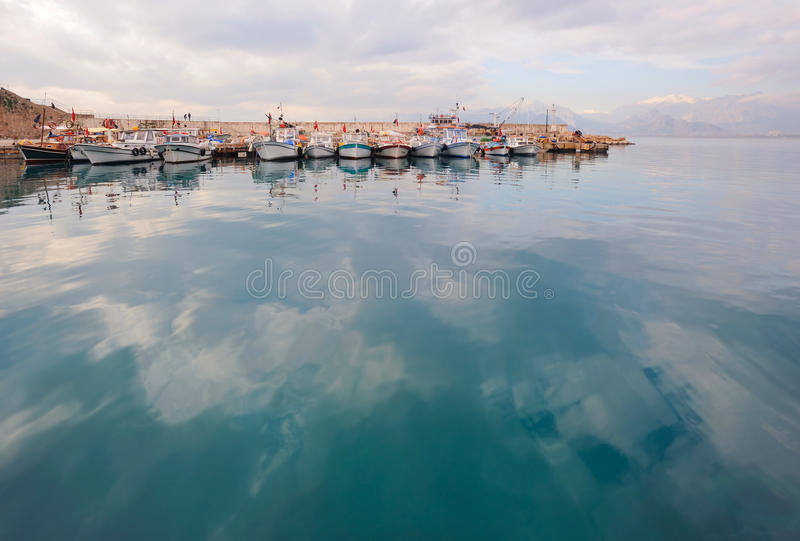 Turkey. Antalya. Mediterranean sea. Port bay. And the ships near pier. Calm sea surface with reflecting clouds royalty free stock images