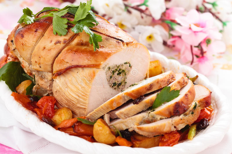 Turkey breast for holidays. Border of stuffed turkey breast with baked vegetables, parsley and spices on plate stock photo