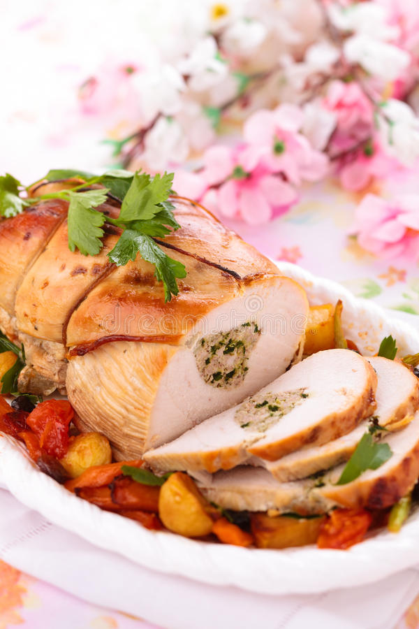 Turkey breast for holidays. Border of stuffed turkey breast with baked vegetables, parsley and spices on plate royalty free stock images