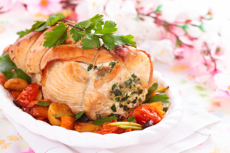 Turkey breast for holidays. Border of stuffed turkey breast with baked vegetables, parsley and spices on plate stock image