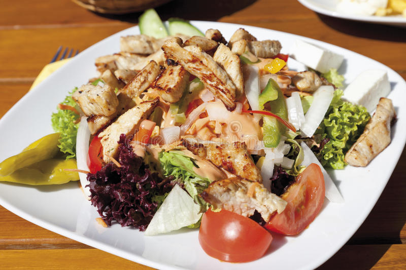 Turkey breast strips with mixed salad and feta cheese royalty free stock image