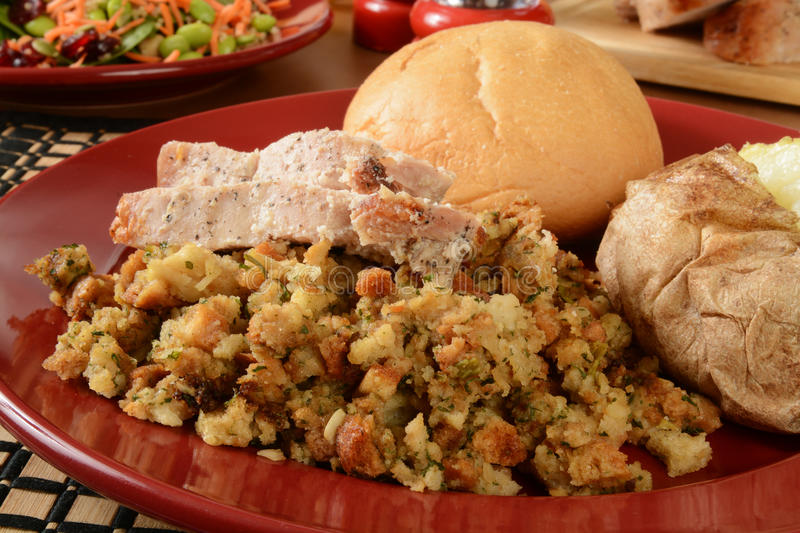 Turkey dinner. Sliced turkey on herbal stuffing with a baked potato and healthy salad stock image