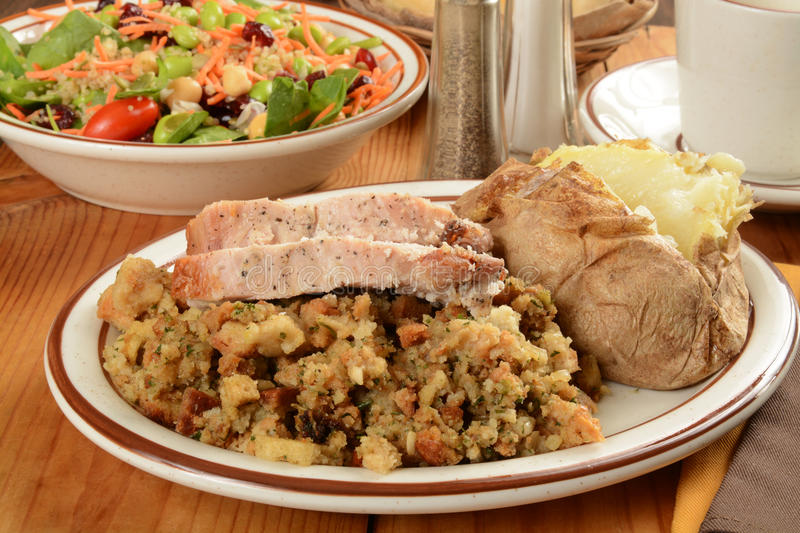 Turkey dinner. Sliced turkey on herbal stuffing with a baked potato and spinach salad stock photos