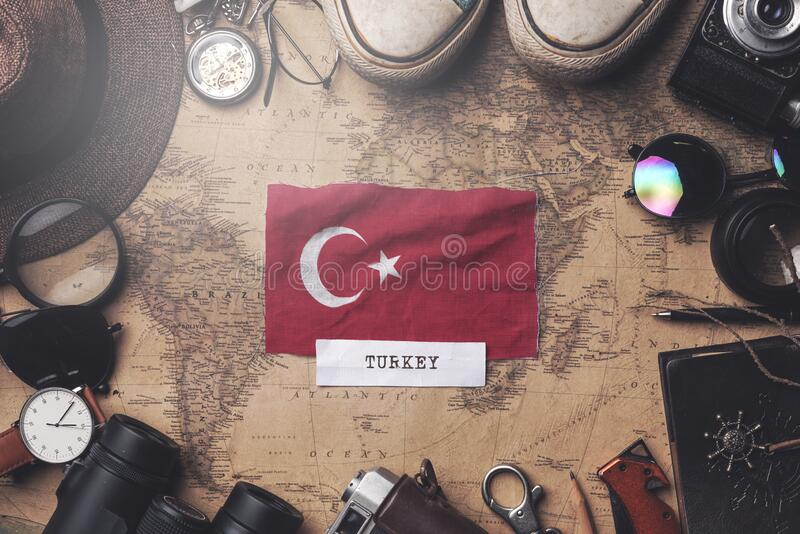 Turkey Flag Between Traveler`s Accessories on Old Vintage Map. Overhead Shot.  stock photo