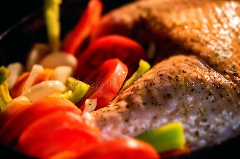 Turkey garnished with vegetables in during cooking stock photography