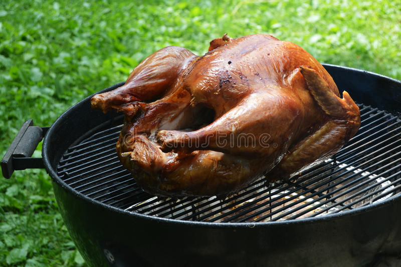 Turkey on Grill. A full turkey being grilled on a charcoal grill stock image