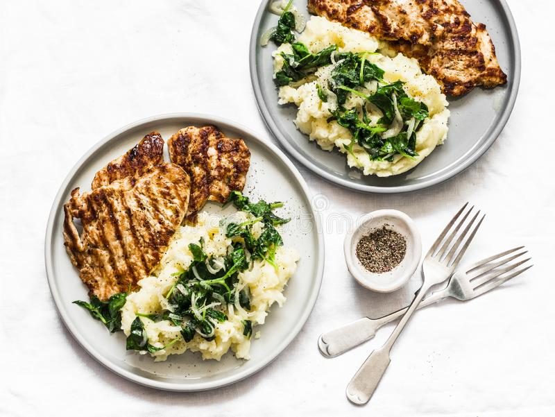 Turkey grilled chop and mashed potatoes with creamy spinach on a light background, top view. Comfort home cooked food stock image