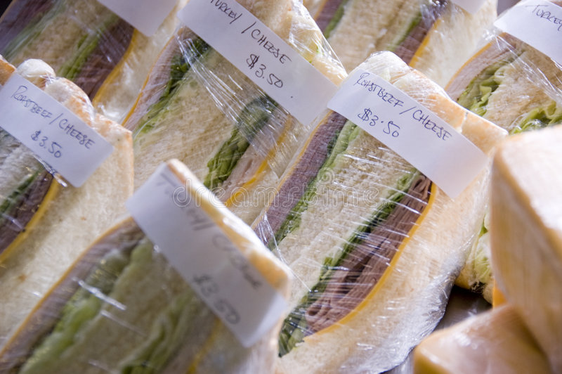 Turkey and Roast Beef Sandwiches. With lettuce and cheese on white toast bread wrapped in plastic wrap stock images