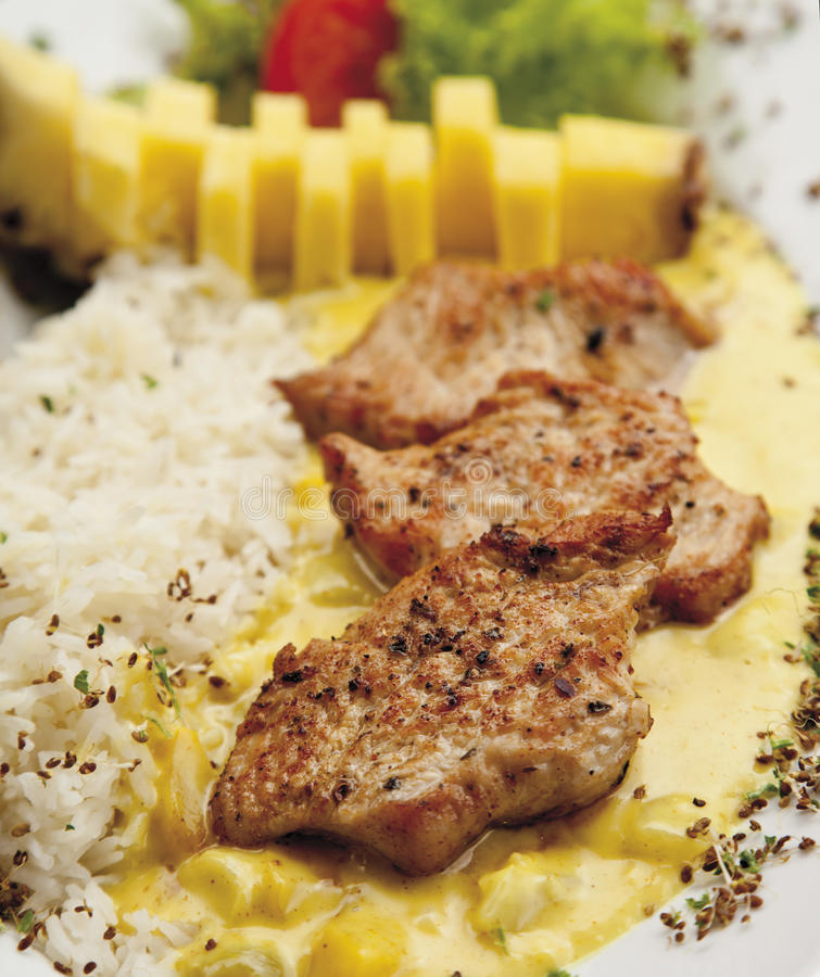 Turkey hen filet garnished with rice, pineapple and curry sauce royalty free stock photo