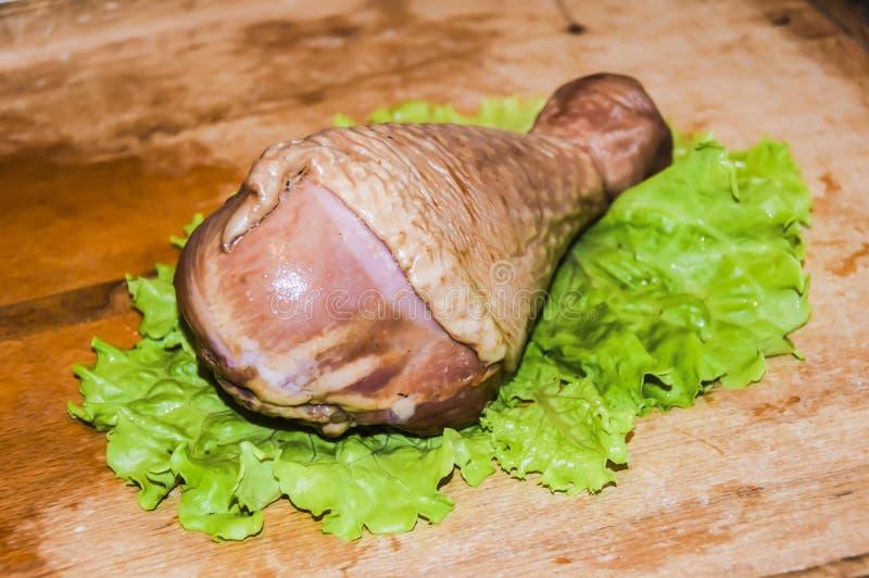 Turkey leg. Smoked turkey leg on a lettuce leaf on a wooden background stock photos