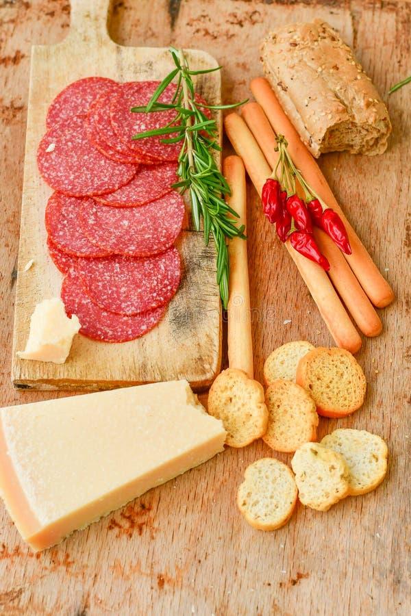 Ingredients for italian snack, bruschetta, crostini or sandwich bar with italian ham, sausage and antipasto on rustic wooden backg. Turkey light Salami sausage stock photo