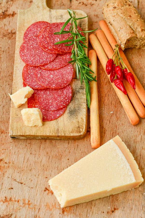 Ingredients for italian snack, bruschetta, crostini or sandwich bar with italian ham, sausage and antipasto on rustic wooden backg. Turkey light Salami sausage royalty free stock images