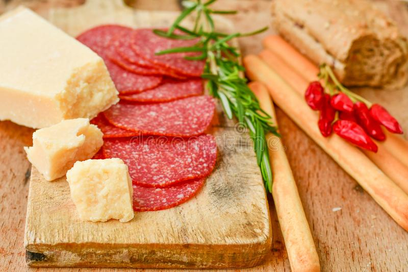 Ingredients for italian snack, bruschetta, crostini or sandwich bar with italian ham, sausage and antipasto on rustic wooden backg. Turkey light Salami sausage stock images