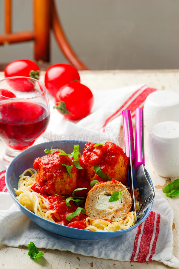 Turkey meat balls stuffed with feta cheese in tomato sauce stock images