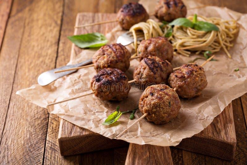 Turkey meatballs on wooden skewers. With pesto pasta stock photos