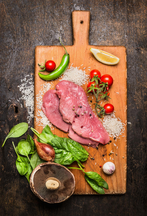 Turkey steak on a cutting board with mushrooms and green peppers tomatoes and lemon garlic on wooden rustic background top view. Turkey steak on cutting board stock images