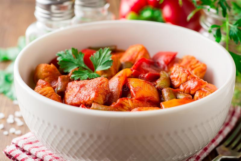 Turkiet ragu med spanska peppar, haricot vert och tomater i bunke på den mörka trätabellen royaltyfria foton