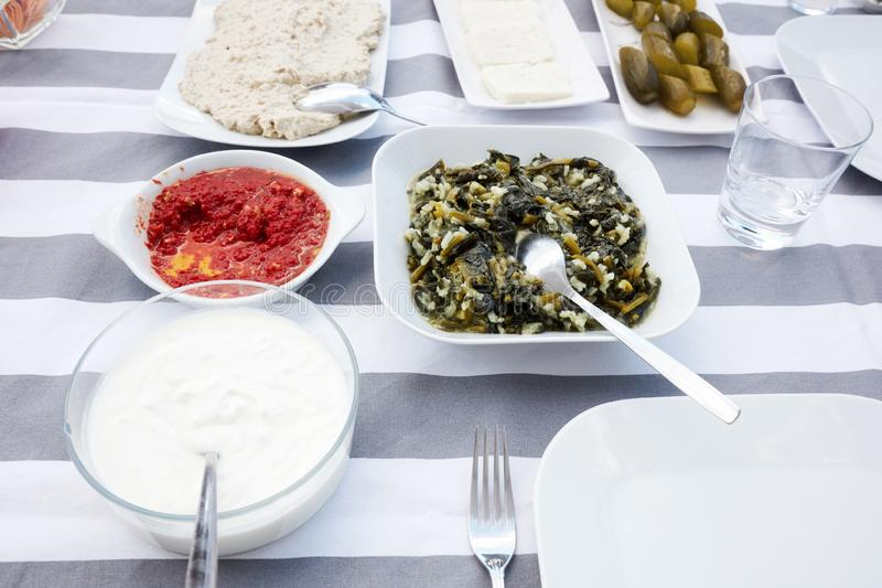 Turkish appetizers cooked chard, yogurt, white cheese, mashed tomatoes, hummus and pickles served on a table. Under natural afternoon light royalty free stock photos